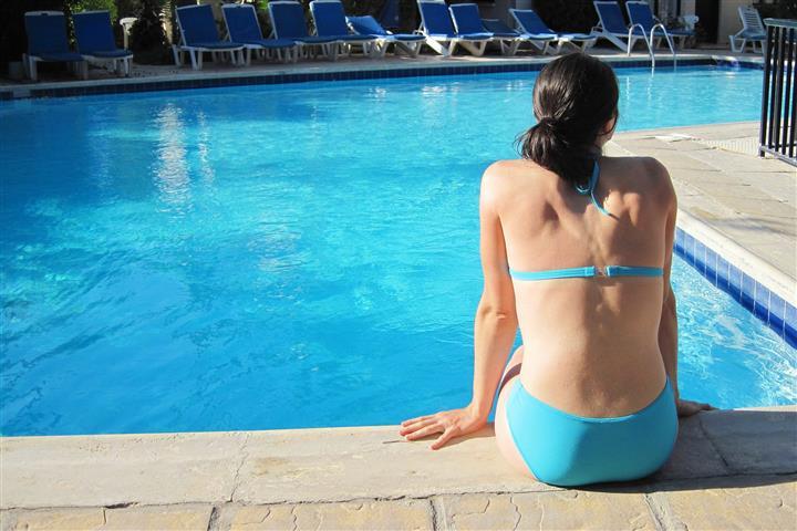 Bikinis nő medence mellett